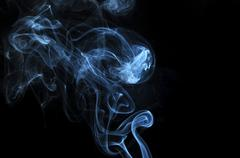 abstract illuminated smoke isolated on a pitch black background - stock photo