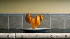 four orange slices floating over a white dish on a kitchen counter top. - stock photo