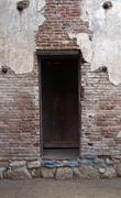 Door way entrance to a building with old red adobe bricks and worn down plast Stock Photos