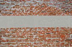 hand made brick wall made from narrow long bricks with a strip of cement plas - stock photo