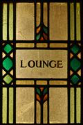 a stained glass lounge sign lit from behind - stock photo