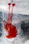Red food coloring dye being dropped into a watertank fishtank Stock Photos