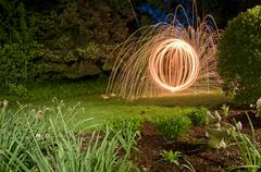 Spinning lit steel wool sparks in the garden at night Stock Photos