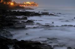 Beautiful ocean sea rocks with misty fog and an illuminated ocean-view hotel Kuvituskuvat