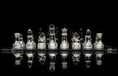 glass chess pieces on a glass chessboard with a reflection isolated on a blac - stock photo