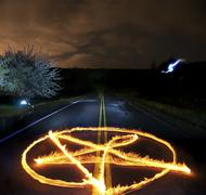 pantagram made of fire flames in the middle of a country rural road at night - stock photo
