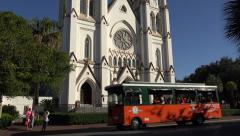 Trolley bus passes st john the baptist cathedral, savannah, ga, usa Stock Footage