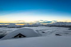 house covered with snow in the high mountains - stock photo
