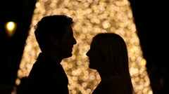 Silhouette of young couple on blurred light background Stock Footage