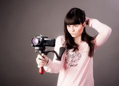 young woman with video camera - stock photo