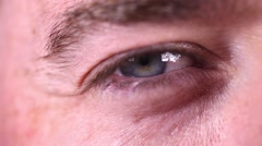 Attractive male blue eye iris contracting close up. Mysterious smile - stock footage
