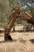 A backhoe digging up some dirt holes in the ground. Stock Photos