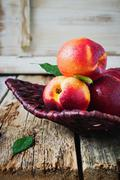 Nectarine in a wicker plate. Stock Photos