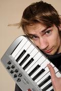 young man holding his midi keyboard - stock photo