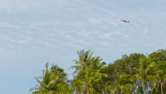 Phuket, thailand - circa nov 2014: red commercial jetplane flying over tall t Stock Footage