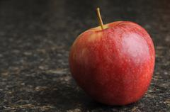 a red apple on a black kitchen countertop. - stock photo