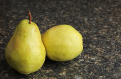 a pair of pears on a black kitchen countertop - stock photo