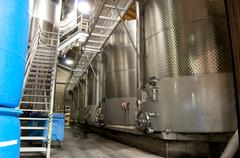 Large stainless steel vats of wine inside of a winery factor. Stock Photos