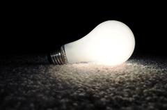 Unscrewed illuminated light bulb on the floor, brightly lit in the darkness. Stock Photos