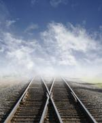 Stock Photo of two railroad tracks lead off into the daylight foggy sky with clouds.