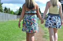 two beautiful young blond ladies in a dress and skirt walk down a dirt pathwa - stock photo