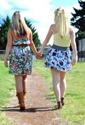 Two beautiful young blond ladies in a dress and skirt walk down a dirt pathwa Stock Photos