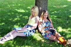 girls reading books under tree in shade - stock photo