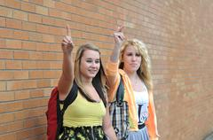 two teenage girls waving their raised hands and fingers up trying to get a ri - stock photo