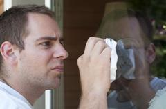 Stock Photo of a young man cleaning the window on his house with a paper towel.