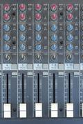 A multi-channel hardware audio mixer with microphone. Stock Photos