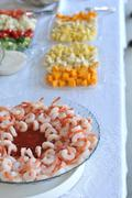 a bunch of shrimp arranged in a bowl with red sweet sauce for dip. - stock photo