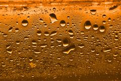 orange condensation waterdrops on  glass with a back light. - stock photo