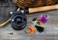 fishing gear on rustic wood - stock photo