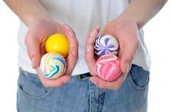 Hand holding a set of four round bouncy rubber balls with colorful designs on Stock Photos