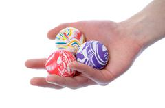 Hand holding a set of round bouncy rubber balls with colorful designs on them Stock Photos