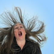 A woman screaming in front of a blue background with her hair blasting behind Stock Photos