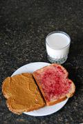 open peanut butter and jelly sandwich on a counter top with a glass of milk b - stock photo