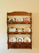 antique miniature butter pat plates on an old wooden shelf hanging on a wall - stock photo