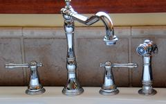 Closeup of a kitchen sink faucet and handles Stock Photos