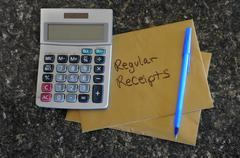 a blank calculator with a gold envelope that says regular receipts - stock photo