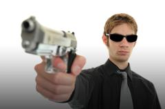 young man holding up a gun with the focus on his face. he is wearing sunglass - stock photo