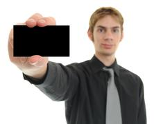 Young businessman holds up his black blank business card Stock Photos