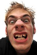 Stock Photo of angry ugly man with crooked teeth and glasses isolated on white