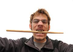 drummer biting his drumstick with braces on white background. - stock photo