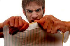 Angry young man ripping trying to papers on white background. background is b Stock Photos