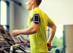 man with smartphone exercising on treadmill in gym - stock photo
