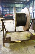 Wooden reel with steel wire rope in hargar Stock Photos