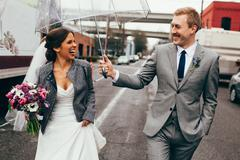 Bride and groom laughing with umbrella Stock Photos