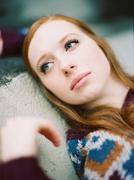 portrait of young woman with red hair blue eyes laying down - stock photo
