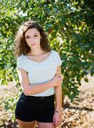 Portrait of young woman in front of tree holding arm Stock Photos